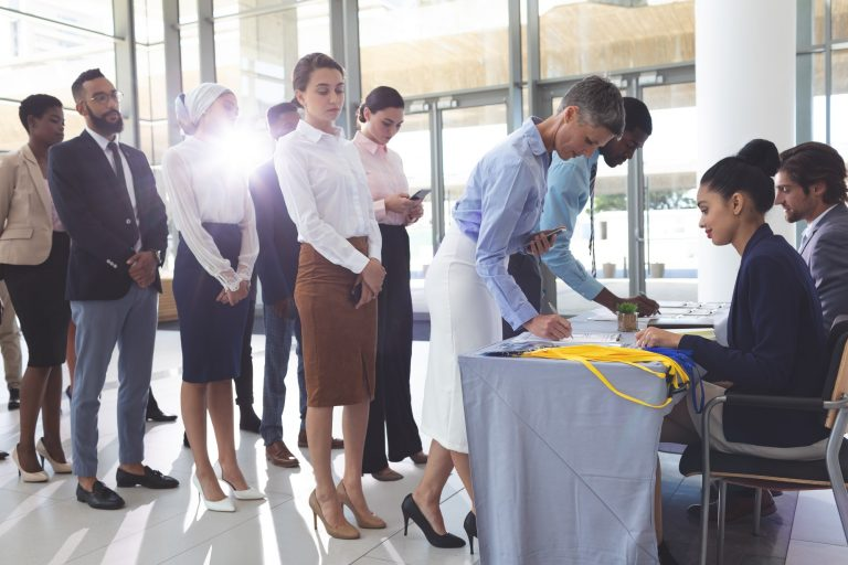 Businesswoman and businessman signing in at conference registration table while group