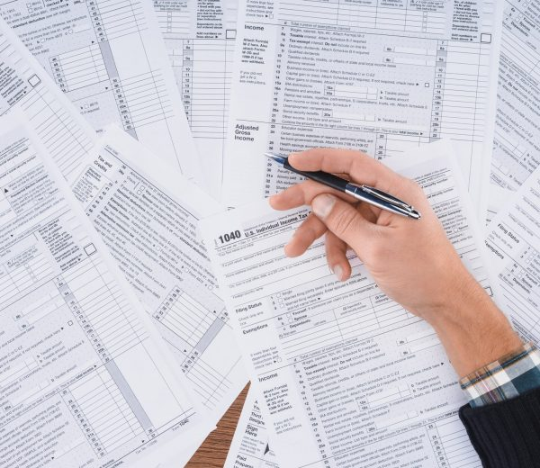 partial view of man holding pen and filling tax forms with copy space
